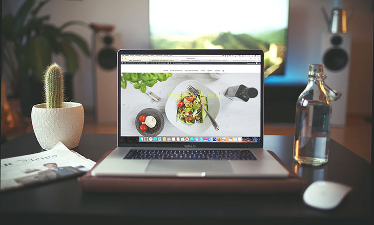 laptop on desktop displaying food website